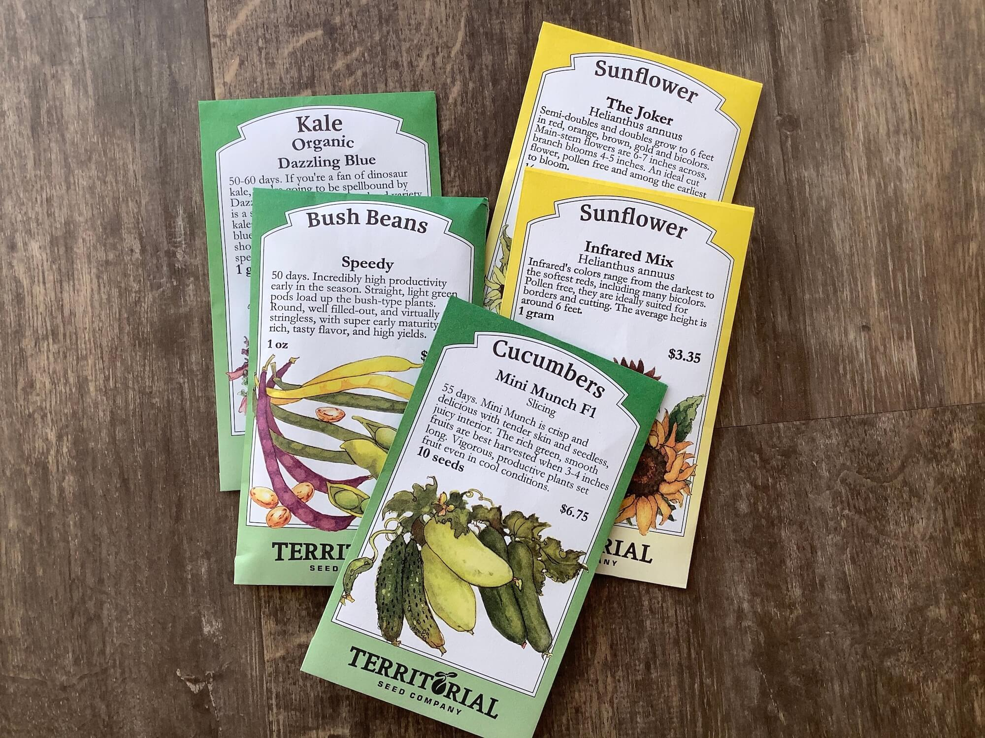 A photo of five seed packets, mini munch cucumbers, speedy bush beans, the joker sunflowers, infrared mix sunflowers and dazzling blue kale